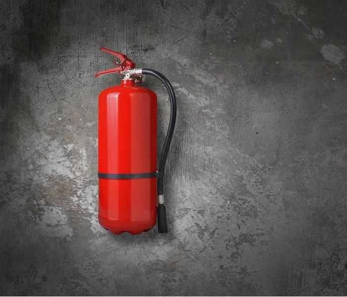 a red fire extinguisher hanging on gray concrete wall